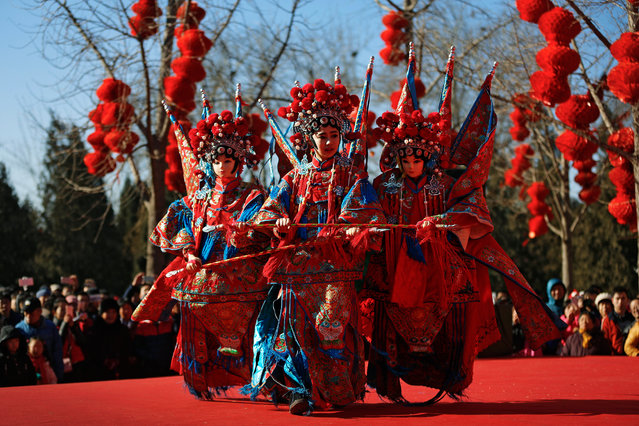 A Chinese dancer dressed in traditional costume performs a cultural dance on stage during a temple fair for a Lunar New Year celebration in Beijing, Monday, February 8, 2016. (Photo by Andy Wong/AP Photo)