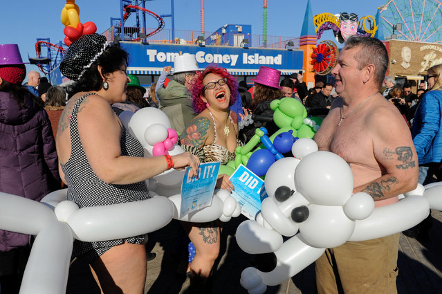 People dance on the boardwalk after participating in the annual Polar Bear Plunge in Coney Island in the Brooklyn Borough of New York City, U.S. January 1, 2017. (Photo by Stephanie Keith/Reuters)