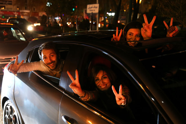 Iranians flash the victory sign from their car while celebrating on a street in northern Tehran, Iran, Thursday, April 2, 2015, after Iran's nuclear agreement with world powers in Lausanne, Switzerland. (Photo by Ebrahim Noroozi/AP Photo)