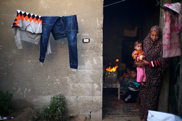 A Palestinian woman holds her child as her sons warm themselves by a fire inside their dwelling on a rainy day in Khan Younis in the southern Gaza Strip December 14, 2016. (Photo by Ibraheem Abu Mustafa/Reuters)