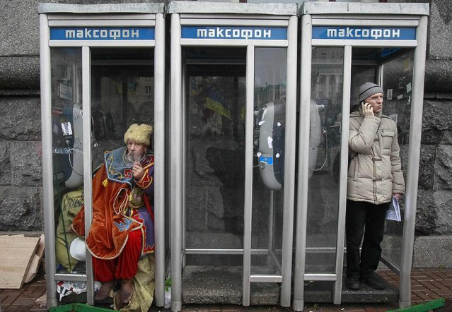 A man dressed in traditional Ukrainian Cossack clothes smokes in a phonebooth during a rally to support EU integration in Kiev December 6, 2013. Ukrainian President Viktor Yanukovich was flying to Russia on Friday to meet Vladimir Putin, a news agency reported, seeking aid to shore up a creaking economy while protesters back home, opposed to his U-turn away from Europe, defied police. (Photo by Gleb Garanich/Reuters)