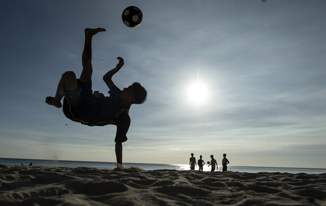 A boy plays football along a beach on the Philippine island of Boracay on October 25, 2018. The Philippines re-opens its crown jewel resort island Boracay to holidaymakers on October 26, after a six-month clean up aimed at repairing the damage inflicted by years of unrestrained mass tourism. (Photo by Noel Celis/AFP Photo)