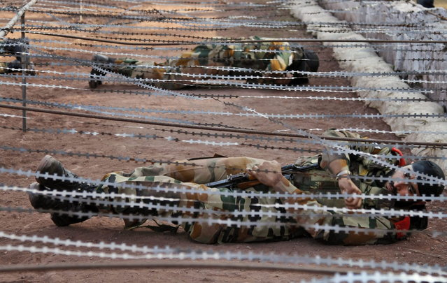 In this Tuesday, December 24, 2013 photo, Indian army soldiers cross an obstacle course, during a training session at a battle school in Rajouri, about 138 kilometers (86 miles) northwest of Jammu, India. (Photo by Channi Anand/AP Photo)