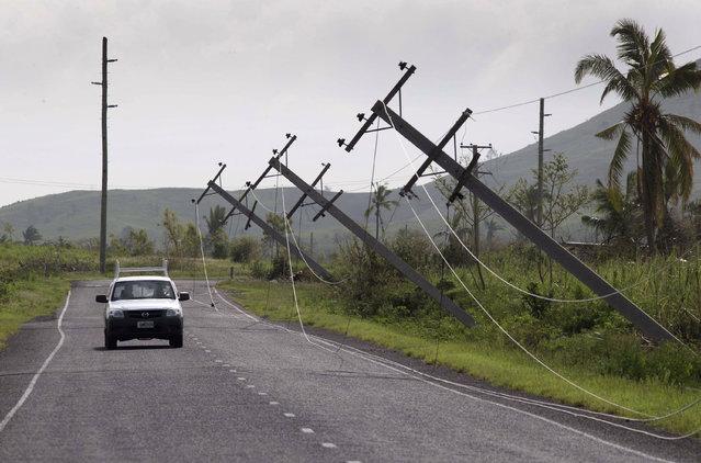 A car drives along Kings Road near Lautoka, Fiji, Wednesday, February 24, 2016, where power poles lean over after cyclone Winston ripped through the island nation. (Photo by Brett Phibbs/New Zealand Herald via AP Photo)