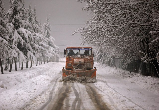 A snow-clearing vehicle removes snow from a road during snowfall in Srinagar January 16, 2017. (Photo by Danish Ismail/Reuters)