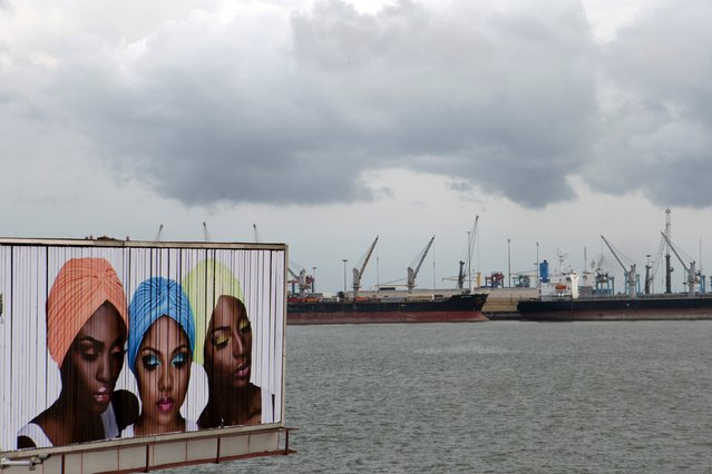 A sign for cosmetic products is seen in front of ships lined up at the Apapa port in Lagos, Nigeria, April 11, 2015. (Photo by Joe Penney/Reuters)