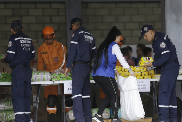 Venezuelan volunteers, Colombian firefighters and rescue workers prepare USAID humanitarian aid for storage at a warehouse next to the Tienditas International Bridge, near Cucuta, Colombia, on the border with Venezuela, Friday, February 8, 2019. Trucks carrying U.S. humanitarian aid destined for Venezuela arrived Thursday at the Colombian border, where opposition leaders vowed to bring them into their troubled nation despite objections from embattled President Nicolas Maduro. (Photoby Fernando Vergara/AP Photo)