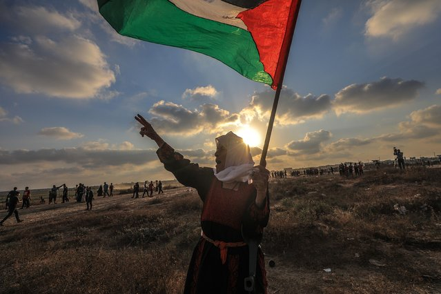 A Palestinian elderly woman protester holds up a Palestinian flag during the clahses near the border between Israel and Gaza Strip, in the eastern Gaza Strip, 21 August 2021. Forty one Palestinians and one Israeli soldier were injured during the clashes near the border east Gaza City. (Photo by Mohammed Saber/EPA/EFE)