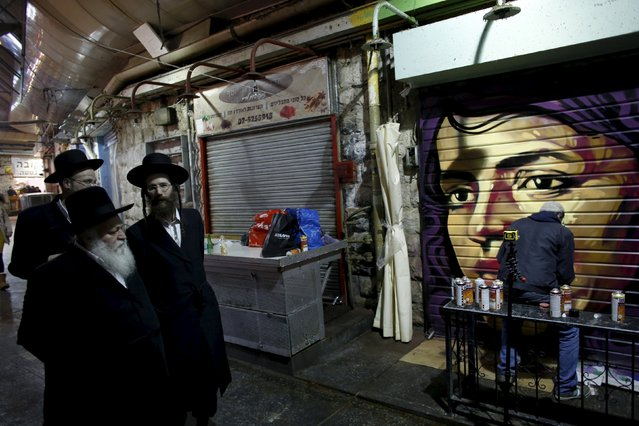 Ultra-Orthodox Jewish men (L) walk past artist Solomon Souza, 22, as he spray-paints a portrait on the metal shutter of a closed storefront in Mahane Yehuda, one of Jerusalem's most popular outdoor markets February 24, 2016. (Photo by Ronen Zvulun/Reuters)