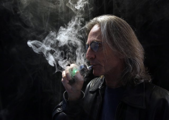 In this Wednesday, December 4, 2013 file photo, John Hartigan, proprietor of Vapeology LA, a store selling electronic cigarettes and related items, takes a puff of an electronic cigarette at his store in Los Angeles. (Photo by Reed Saxon/AP Photo)