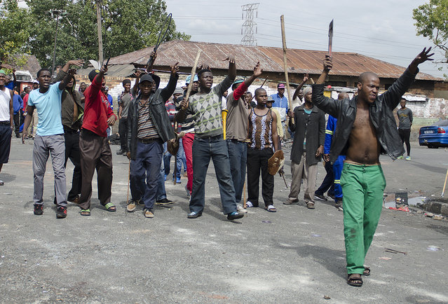 South African hostel dwellers demonstrate against foreigners in Johannesburg, Friday, April 17, 2015, after overnight attacks between locals and immigrants in Johannesburg. Several shops and cars were torched overnight in continued anti-immigrant attacks, despite an appeal from President Jacob Zuma to stop the violence. (Photo by Shiraaz Mohamed/AP Photo)