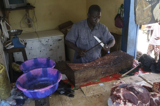 A man sells meat on a street in Conakry, Guinea, Thursday, September 9, 2021. Guinea's new military leaders sought to tighten their grip on power after overthrowing President Alpha Conde, warning local officials that refusing to appear at a meeting convened Monday would be considered an act of rebellion against the junta. (Photo by Sunday Alamba/AP Photo)