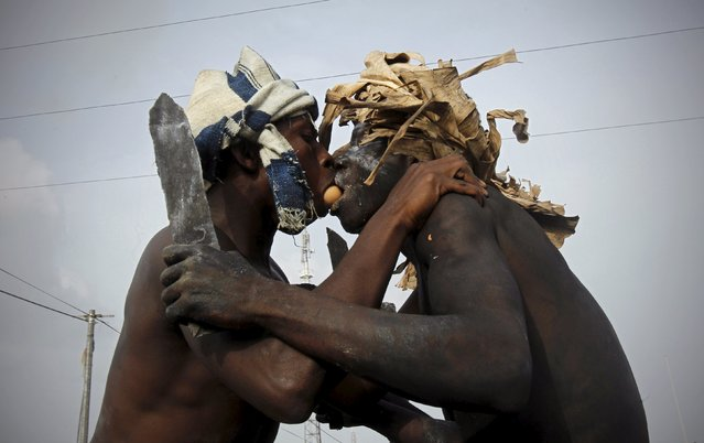 Participants pass an egg using their mouths during a religious ritual as they play the role of traditional fighters in a parade during the Popo (Mask) Carnival of Bonoua, in the east of Abidjan, April 18, 2015. The carnival has its origins in the changes that Aboure youths in Bonoua introduced to the annual festival of yams. (Photo by Luc Gnago/Reuters)