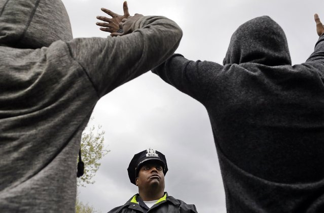 A member of the Baltimore Police Department stands guard outside of the department's Western District police station as men hold their hands up in protest during a march for Freddie Gray, Wednesday, April 22, 2015, in Baltimore. Gray died from spinal injuries about a week after he was arrested and transported in a police van. (Photo by Patrick Semansky/AP Photo)