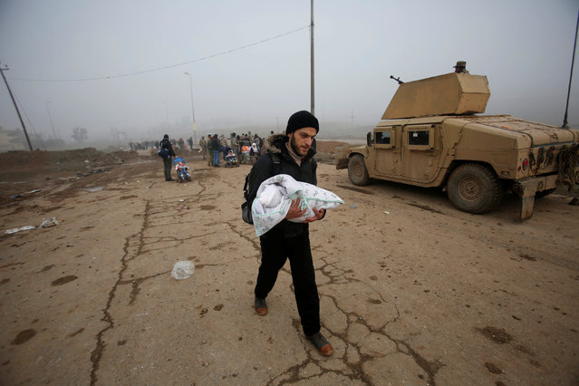 A man carries his child as he flees his home as Iraqi forces battle with Islamic State militants in Arabi neighborhood, north of Mosul, Iraq, January 23, 2017. (Photo by Khalid al Mousily/Reuters)