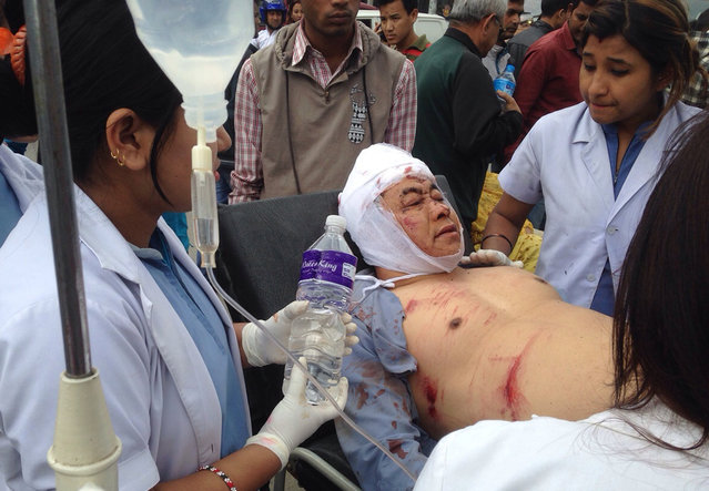 An Injured person receives treatment outside the Medicare Hospital in Kathmandu, Nepal, Saturday, April 25, 2015. (Photo by Niranjan Shrestha/AP Photo)