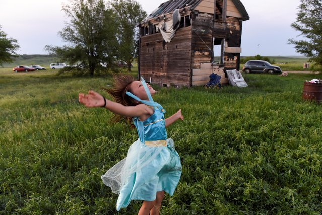 One of Beatrice Lookinghorse's granddaughters, Rozelynn Whitebull, plays near an abandoned house in the backyard of Beatrice Lookinghorse's trailer on the Cheyenne River Reservation in Green Grass, South Dakota, U.S., May 31, 2018. (Photo by Stephanie Keith/Reuters)