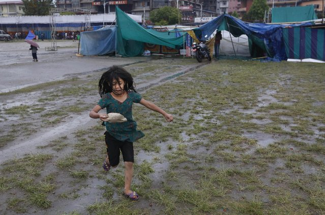 A Nepalese girl, a victim of recent earthquake, with food snacks in her hand runs back to her makeshift tent amidst a sudden rain in Kathmandu, Nepal, Tuesday, April 28, 2015. (Photo by Manish Swarup/AP Photo)