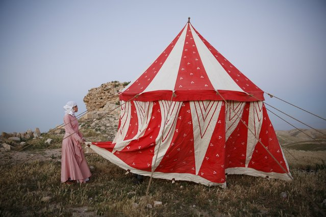 A history enthusiast dressed in a costume helps to erect a tent at a campsite during an event to relive the experiences of pilgrims who travelled to Jerusalem during medieval times, at a historical fortress near the settlement of Ma'ale Adumim in the West Bank, east of Jerusalem, March 10, 2016. (Photo by Baz Ratner/Reuters)