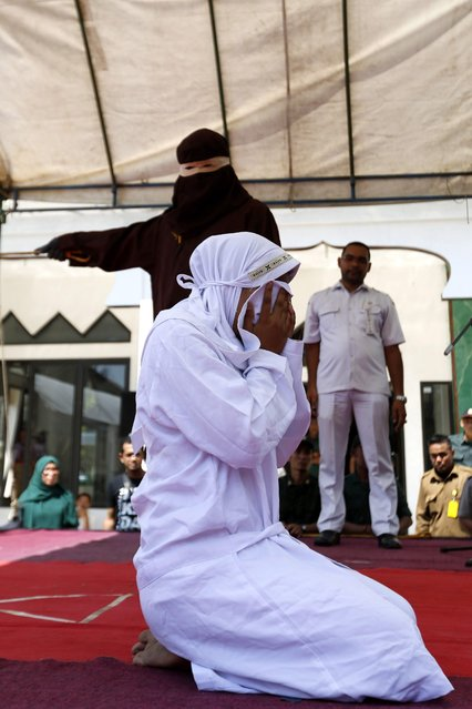 An Acehnese woman covers her face while being whipped in front of the public for violating sharia law in Banda Aceh, Indonesia, 02 February 2017. (Photo by Hotli Simanjuntak/EPA)
