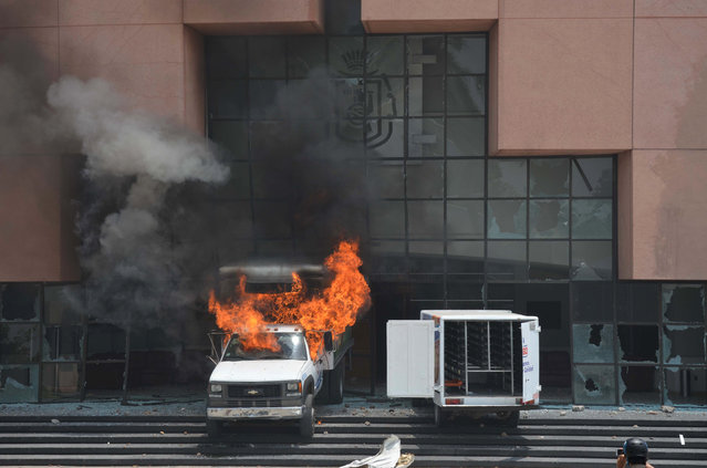 A dairy product delivery truck burns next to another delivery truck after they were rammed by protesters into the main entrance of the state congress building in Chilpancingo, Mexico, Sunday, April 26, 2015. Students belonging to the Ayotzinapa rural teachers college protested violently on the seventh month anniversary of the disappearance of 43 of their fellow students at the hands of organized crime with the aid of corrupt local authorities. (Photo by Alejandrino Gonzalez/AP Photo)