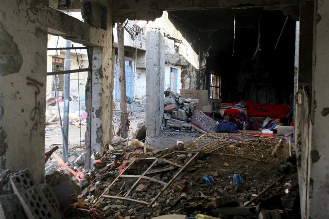 A man rests inside a building destroyed during recent fighting in Yemen's southwestern city of Taiz March 14, 2016. (Photo by Anees Mahyoub/Reuters)