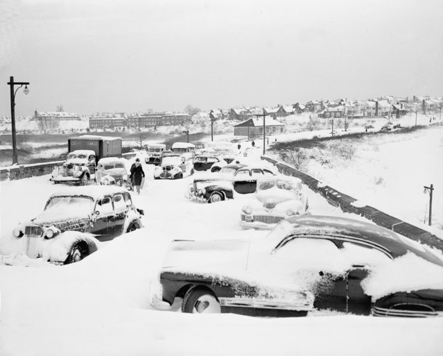 Pedestrians make their way in between cars stalled on the bridge while crossing the Grand Central Parkway at Union Turnpike, Kew Gardens, Queens, N.Y., December 27, 1947.   A record-breaking 25.8 inch snowfall caused 21 cars, 3 buses and 2 trucks to be abandoned in the drift in this area. (Photo by AP Photo)