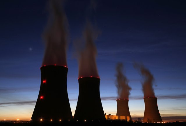 Steam rises at night from the cooling towers of the Electricite de France (EDF) nuclear power station in Dampierre-en-Burly, March 8, 2015. (Photo by Christian Hartmann/Reuters)