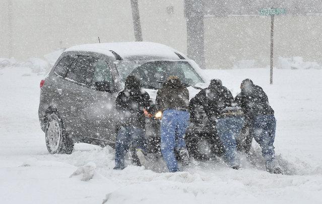 Good Samaritans help push a stranded motorist stuck in deep snow in Bethlehem, Pennsylvania. (Photo by Chris Post/Associated Press)