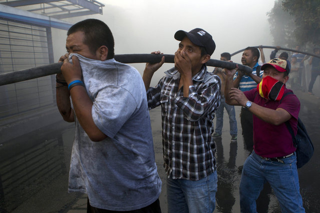 Vendors hold water hoses as they help firefighters control a fire in a tire warehouse in La Terminal, the largest and most important market in Guatemala City, Wednesday, May 6, 2015. (Photo by Moises Castillo/AP Photo)