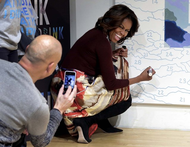 Artist Trey Speegle photographs first lady Michelle Obama as she prepares to autograph his color-by-numbers mural featuring the slogan for WAT-AAH!, a line of bottled water targeted to kids and teens, at the New Museum in New York, on February 20, 2014. (Photo by Richard Drew/Associated Press)