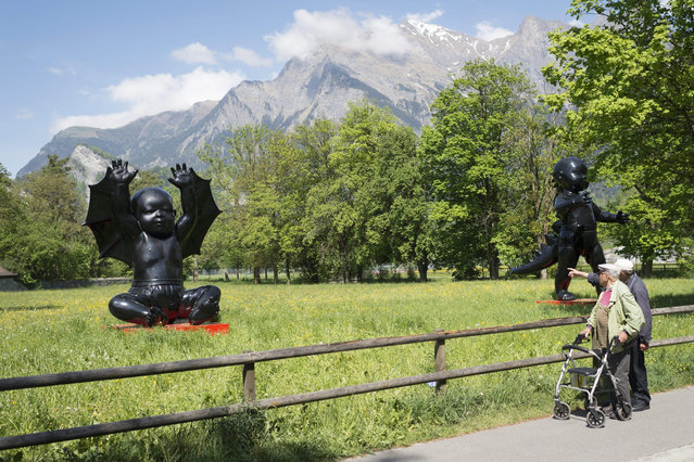 "Two men stop looking at the sculptures ""Angel Demon3"" by Russian artist AES+F, during the 6th Swiss Triennal Festival of Sculpture ""Bad RagARTz"", in Bad Ragaz, Switzerland, 07 May 2015. The festival showing about 400 sculptures by 90 artists from 13 countries are shown in public areas from May to November. (Photo by Gian Ehrenzeller/EPA)"