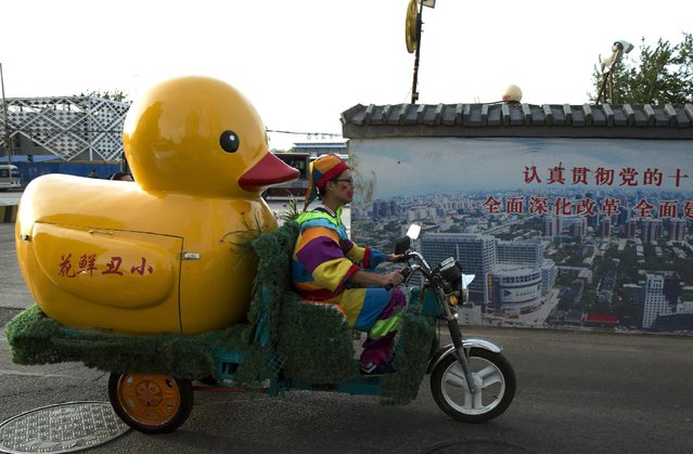 A delivery man for a florist dressed as a clown makes his rounds past government slogans calling for deepening reforms in Beijing Tuesday, May 5, 2015. Government propaganda is a common sight in the Chinese capital, a reminder it is also the political center of China. (Photo by Ng Han Guan/AP Photo)