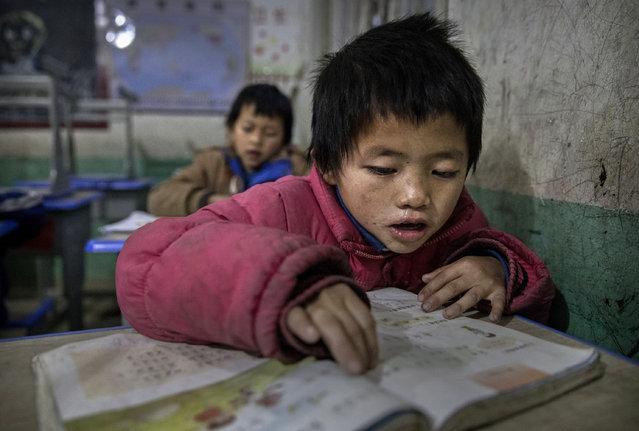 """""""Left behind"""" child Luo Hongniu, 8 (R) reads in class at a local school on December 16, 2016 in Anshun, China. (Photo by Kevin Frayer/Getty Images)"""