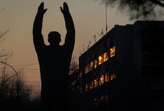 The sun is reflected in a building behind a sculpture of the first cosmonaut Yuri Gagarin at the Russian leased Baikonur cosmodrome, Kazakhstan, Monday, March 11, 2019. The new Soyuz mission to the International Space Station (ISS) is scheduled on Thursday, March. 14 with U.S. astronauts Christina Hammock Koch, Nick Hague, and Russian cosmonaut Alexey Ovchinin. (Photo by Dmitri Lovetsky/AP Photo)