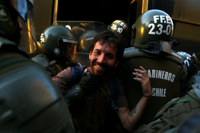A demonstrator is detained during a rally marking the anniversary of the death of workers union leader Juan Pablo Jimenez, in Santiago, Chile February 21, 2017. (Photo by Ivan Alvarado/Reuters)