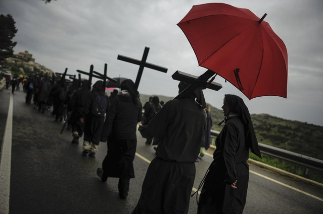 A Catholic penitent of Ujue Virgin shelters from the rain with an umbrella as he takes part in a pilgrimage from Tafalla to the small town of Ujue, northern Spain, Sunday, April 26, 2015. (Photo by Alvaro Barrientos/AP Photo)