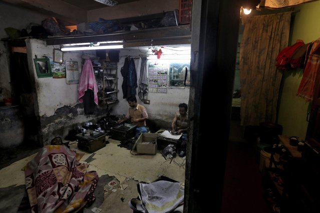 Indian laborers make leather goods while another rests at their home workshop in Calcutta, eastern India, 17 February 2014. (Photo by Piyal Adhikary/EPA)