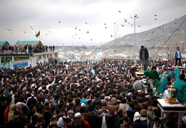 Afghans gather near a shrine to celebrate the Afghan New Year (Newroz) in Kabul March 21, 2014. Afghanistan uses the Persian calendar which runs from the vernal equinox. The calendar takes as its start date the time when the Prophet Mohammad moved from Mecca to Medina in 621 AD. The current Persian year is 1393. (Photo by Ahmad Masood/Reuters)