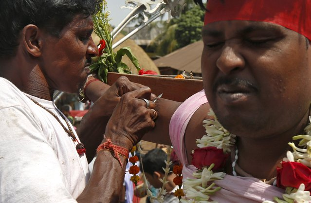 A Hindu devotee react as a metal skewer is pierced through the skin of his arm during the annual Shiva Gajan religious festival in Batanal village in West Bengal, India, April 13, 2016. (Photo by Rupak De Chowdhuri/Reuters)
