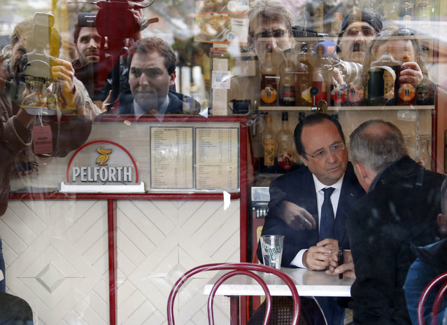 France's President Francois Hollande is seen speaking in a bar after voting in the first round in the French mayoral elections in Tulle, center France, March 23, 2014. The French goes to the polls to cast votes in the two-round 2014 Municipal elections today and on March 30 to elect city mayors and councillors for a six-year term. (Photo by Regis Duvignau/Reuters)