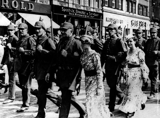 1914: Soldiers accompanied by their wives and girlfriends on the march during the mobilization of German forces