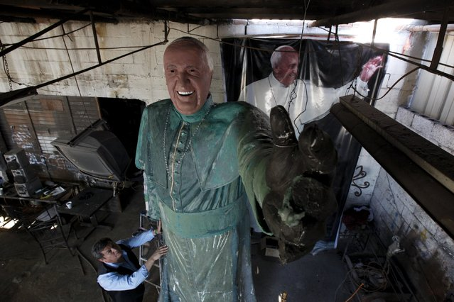 Sculptor Pedro Francisco Rodriguez touches his 16-feet bronze statue of Pope Francis, to be displayed to the public in May, at his workshop in Ciudad Juarez, Mexico, April 20, 2016. (Photo by Jose Luis Gonzalez/Reuters)