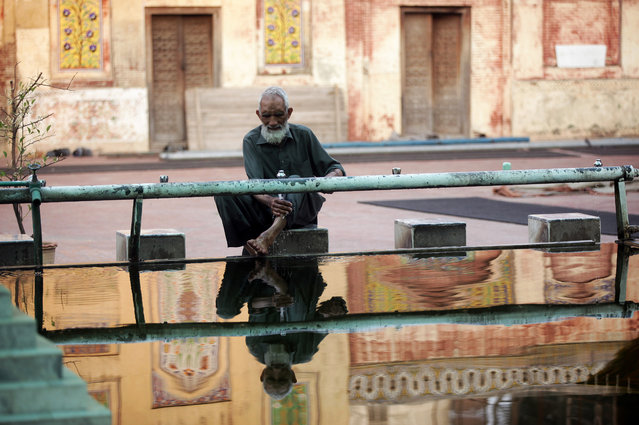 A reflection of a man is seen in a pool of water as washes his feet at a mosque during the fasting month of Ramadan in Lahore, Pakistan, May 16, 2019. (Photo by Mohsin Raza/Reuters)