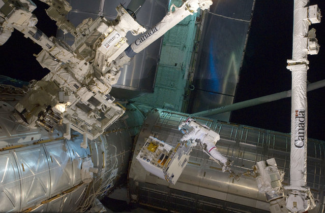 With his feet secured on a restraint on the space station remote manipulator system's robotic arm or Canadarm2, NASA astronaut Mike Fossum (frame center) holds the Robotics Refueling Mission payload, which was the focus of one of the primary chores accomplished on a six and a half hour spacewalk on July 12, 2011. The failed pump module is with DEXTRE on left side of the photo. NASA astronauts Fossum and Ron Garan performed the six-hour, 31-minute spacewalk, which represents the final scheduled extravehicular activity during shuttle missions. (Photo by NASA)