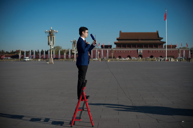 A television journalist stands on a ladder as he reports ahead of the CPPCC Closing ceremony at the Great Hall of the People in Beijing on March 13, 2017. More than 3000 delegates from across China are attending the annual meeting of the country' s rubber- stamp congress. (Photo by Nicolas Asfouri/AFP Photo)