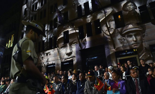 An Australian soldier stands in front of the crowd as a projection is displayed on a building during dawn service to mark the centenary of the Gallipoli landings in Sydney on April 25, 2016. Dawn services were held across the two countries on the anniversary of the ill-fated 1915 campaign of the Australian and New Zealand Army Corps that left 11,500 of them dead in what is now Turkey during World War I. (Photo by Saeed Khan/AFP Photo)