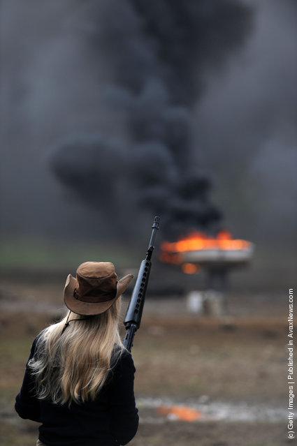 An unidentified woman shoots a M-16 at a range consisting of old cars and boats at the Knob Creek Machine Gun Shoot in West Point, Kentucky