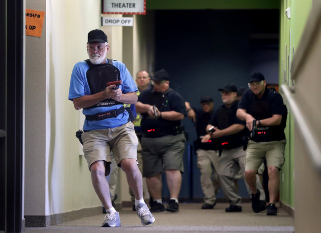 In this July 21, 2019 photo, Stephen Hatherley, left, leads fellow trainees down a hallway as they participate in a simulated gun fight scenario at Fellowship of the Parks campus in Haslet, Texas. While recent mass shootings occurred at a retail store in El Paso, Texas, and a downtown entertainment district in Dayton, Ohio, they were still felt in houses of worship, which haven't been immune to such attacks. And some churches have started protecting themselves with guns. (Photo by Tony Gutierrez/AP Photo)