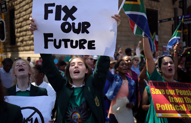 Protesters carry placards outside of the offices of South Africa's outgoing Finance Minister Pravin Gordhan in Pretoria, South Africa, March 31,2017. (Photo by Siphiwe Sibeko/Reuters)